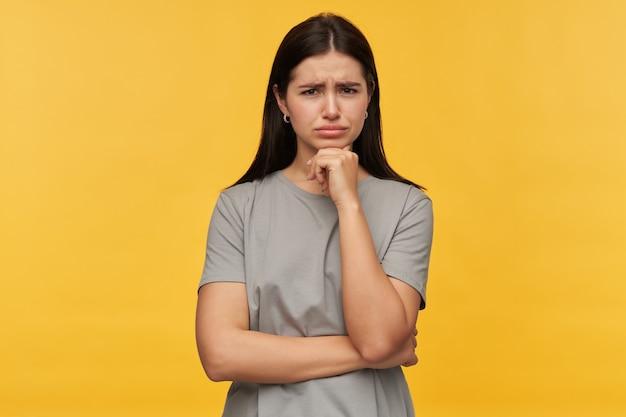 Mulher jovem morena pensativa e concentrada em uma camiseta cinza com as mãos postas e pensando sobre a parede amarela