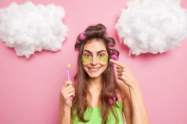 Mulher jovem morena positiva aponta para adesivos de hidrogel e recomenda que produto de beleza segura poses de escova de dentes contra a parede rosa com escova de dentes sorri suavemente