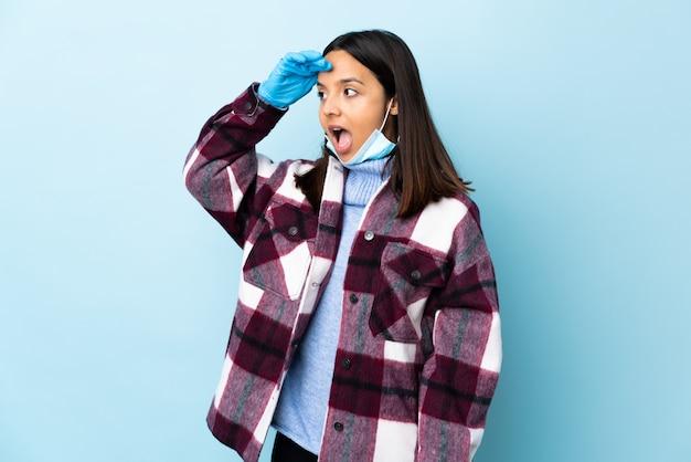 Mulher jovem morena raça mista, protegendo com uma máscara e luvas sobre parede azul com expressão de surpresa enquanto olha de lado