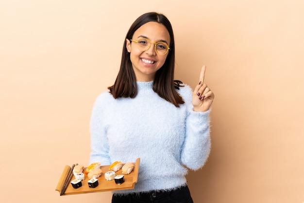 Mulher jovem morena raça mista segurando sushi sobre isolado mostrando e levantando um dedo em sinal dos melhores