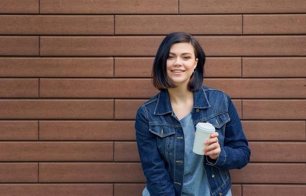 Mulher jovem morena sorridente com túneis nas orelhas em uma jaqueta jeans em frente a parede de tijolos, desfrutando de seu café quente.