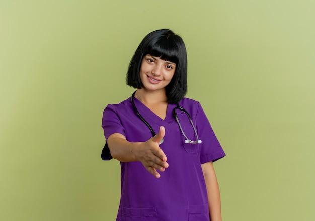 Mulher jovem morena sorridente de uniforme com estetoscópio estende a mão
