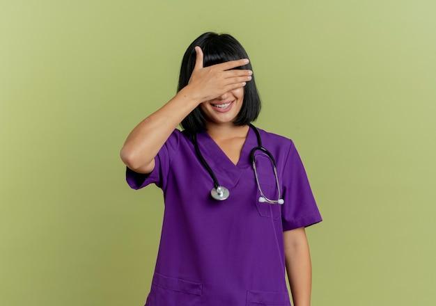 Mulher jovem morena sorridente de uniforme com estetoscópio fecha os olhos com a mão isolada em fundo verde oliva com espaço de cópia