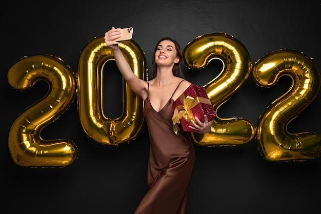 Mulher jovem morena sorridente em um vestido elegante, fazendo selfie em smartphone em fundo preto dourado.