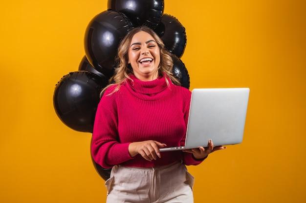 Mulher jovem morena sorridente segurando o computador laptop pc com tela em branco vazia simula o espaço da cópia sobre fundo de cor amarela com retrato de estúdio de balões de ar. venda de sexta feira negra