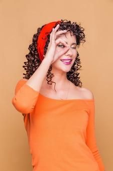 Mulher jovem morena usando lenço e blusa laranja fazendo gesto de ok com a mão sorrindo