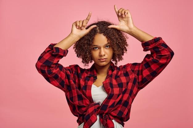 Mulher jovem mostra chifres, parede rosa, emoção. expressão facial, pessoa do sexo feminino olhando para a câmera no estúdio, conceito emocional, sentimentos