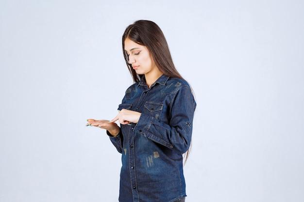 Mulher jovem mostrando algo em sua mão aberta
