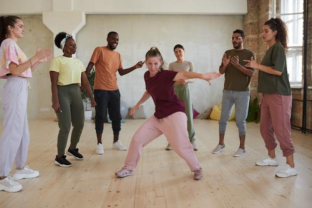 Mulher jovem mostrando exercícios de dança enquanto outras pessoas em círculo batendo palmas e assistindo no estúdio de dança