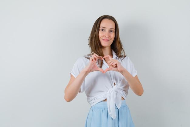 Mulher jovem mostrando formato de coração com dedos em blusa branca e saia azul claro e parecendo feliz
