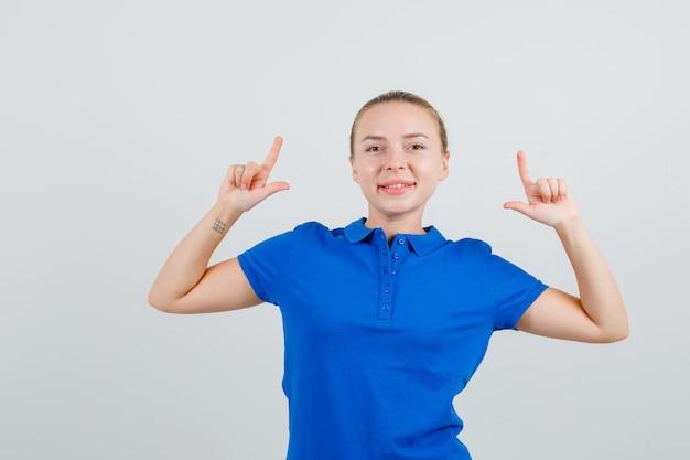 Mulher jovem mostrando gesto de arma em uma camiseta azul e parecendo alegre