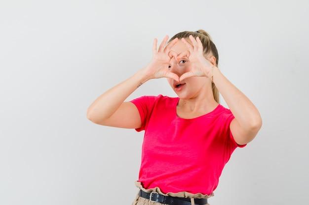 Mulher jovem mostrando gesto de coração em uma camiseta e parecendo alegre