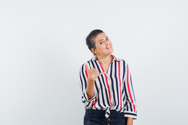 Mulher jovem mostrando gesto de me ligar com uma blusa listrada e parecendo otimista