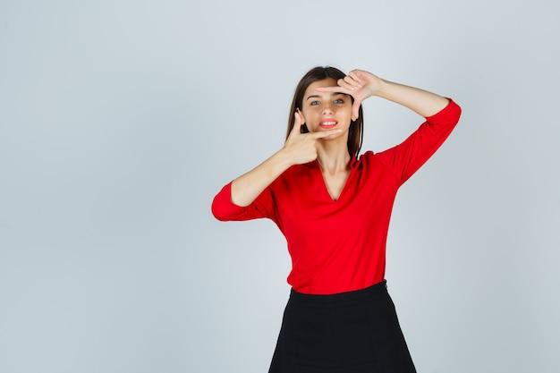 Mulher jovem mostrando gesto de moldura em blusa vermelha, saia preta e parecendo alegre