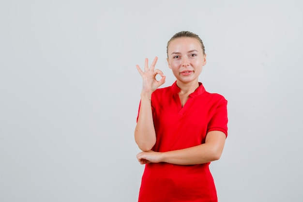 Mulher jovem mostrando gesto de ok em camiseta vermelha e parecendo satisfeita