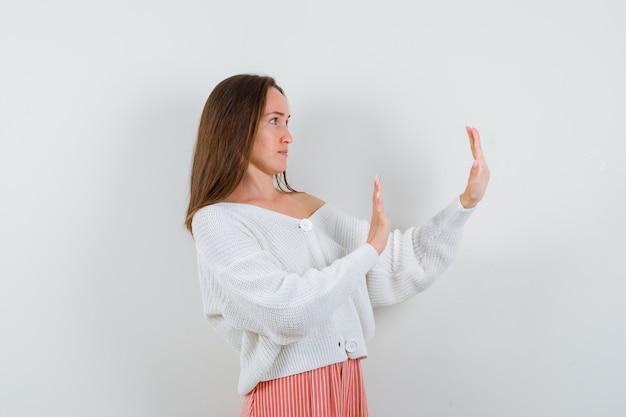 Mulher jovem mostrando gesto de pare em casaquinho e saia parecendo assustada isolada
