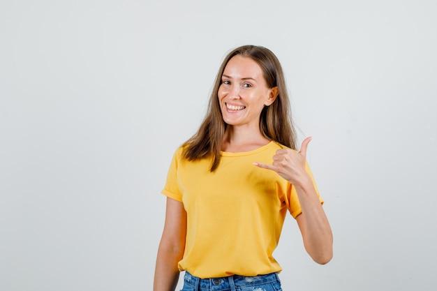 Mulher jovem mostrando gesto de telefone em camiseta, shorts e parecendo alegre