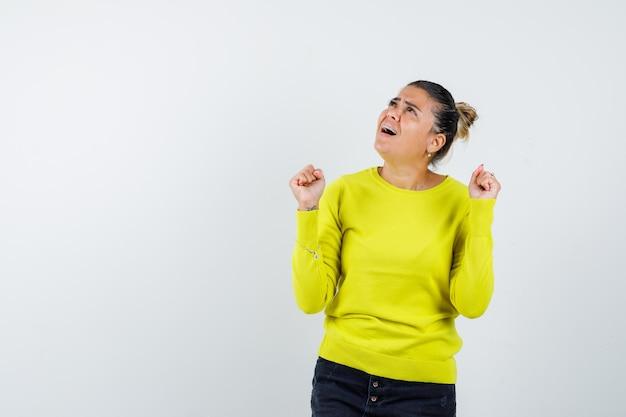 Mulher jovem mostrando gesto de vencedor com suéter amarelo e calça preta e parecendo feliz