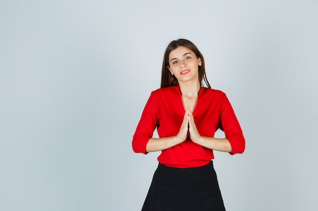 Mulher jovem mostrando gesto namastê com blusa vermelha, saia preta e aparência alegre