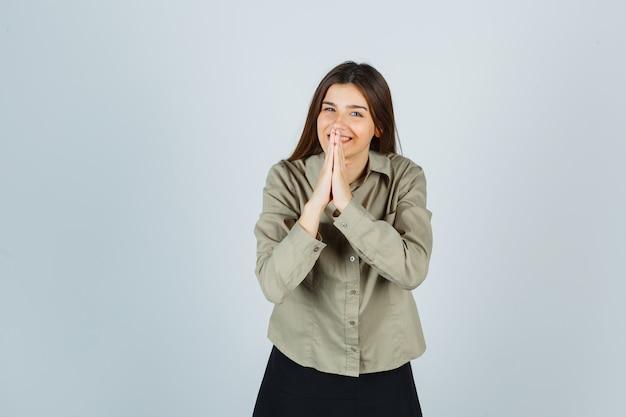 Mulher jovem mostrando gesto namastê na camisa, saia e parecendo alegre