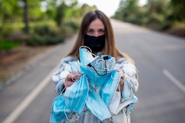 Mulher jovem mostrando máscaras protetoras sujas ao ar livre
