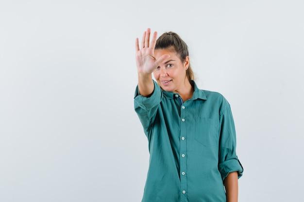 Mulher jovem mostrando o sinal de pare com uma blusa verde e parecendo feliz