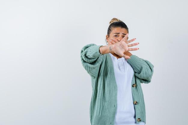 Mulher jovem mostrando o sinal de pare com uma camisa branca e um casaco de lã verde menta e parecendo assustada
