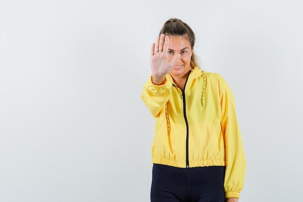 Mulher jovem mostrando o sinal de pare com uma jaqueta de bombardeiro amarela e calça preta e uma aparência fofa