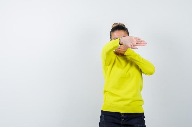 Mulher jovem mostrando o sinal de pare enquanto cobre a boca com um suéter amarelo e calça preta, parecendo séria