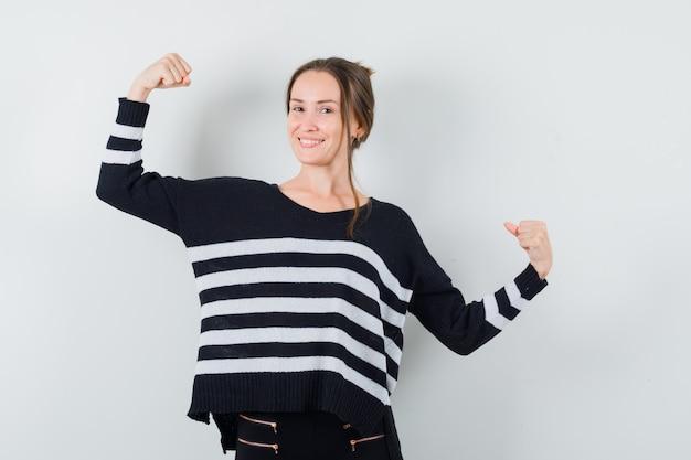 Mulher jovem mostrando os músculos em malhas listradas e calças pretas e parece feliz