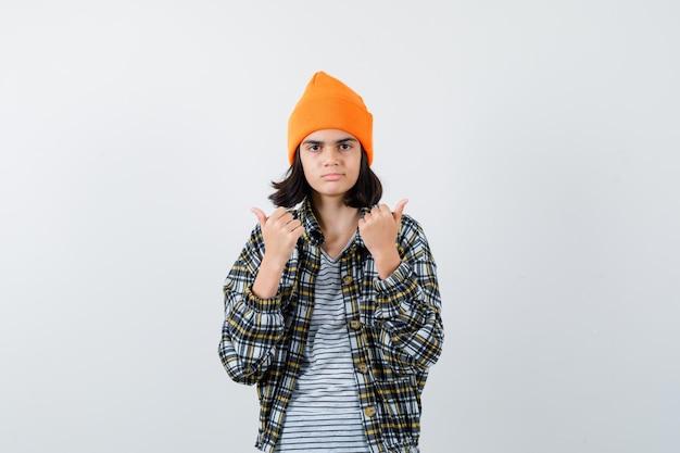 Mulher jovem mostrando os polegares para cima com uma camisa quadriculada de chapéu laranja, parecendo séria