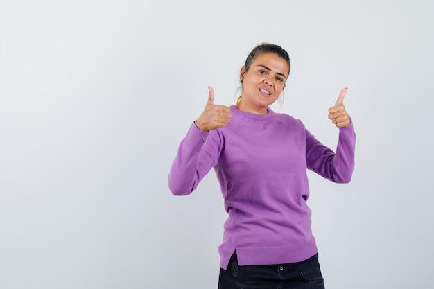 Mulher jovem mostrando os polegares para cima e parecendo feliz