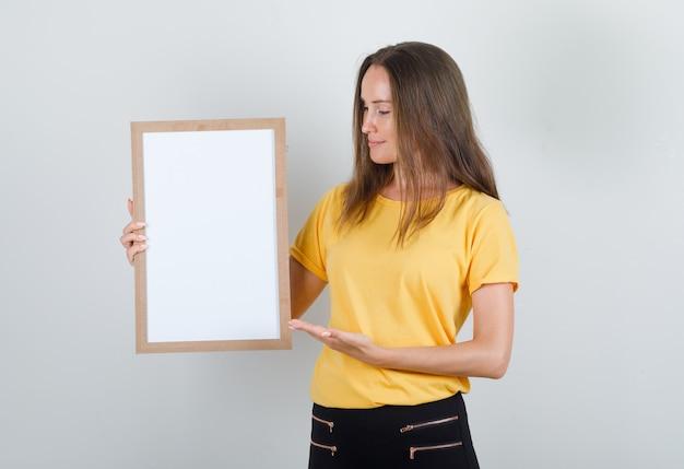Mulher jovem mostrando quadro branco em camiseta, calça e parecendo alegre