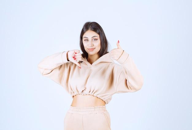 Mulher jovem mostrando sinais de polegar para cima e para baixo