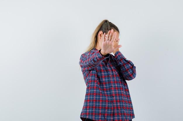 Mulher jovem mostrando sinal de parada em uma camisa e olhando séria Foto gratuita