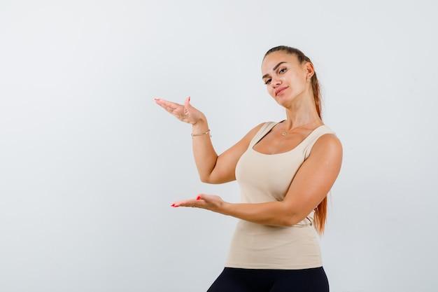 Mulher jovem mostrando sinal de tamanho usando um top bege e parecendo confiante