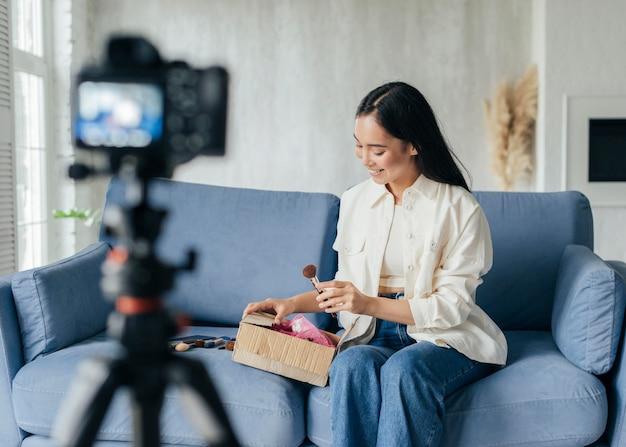 Mulher jovem mostrando suprimentos de maquiagem enquanto faz o vlog