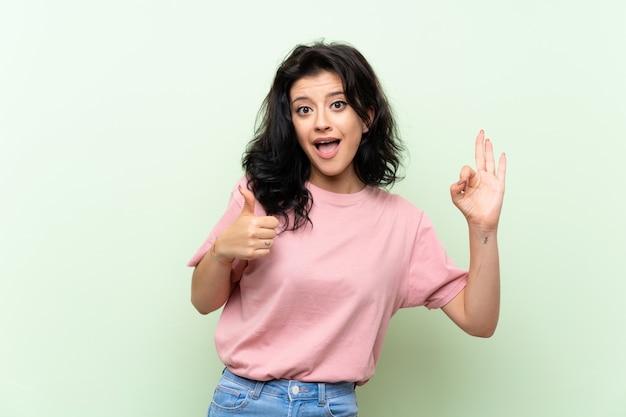 Mulher jovem, mostrando, tá bom sinal, e, polegar cima, gesto