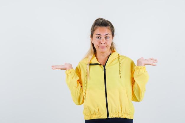 Mulher jovem mostrando um gesto de não sei, com capa de chuva amarela e parecendo confusa