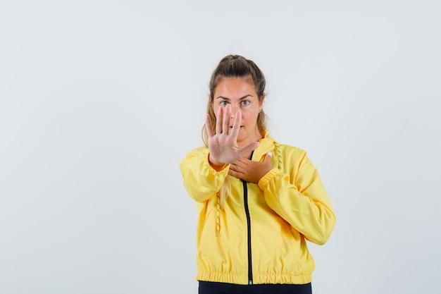 Mulher jovem mostrando um gesto de pare com uma capa de chuva amarela e parecendo relutante