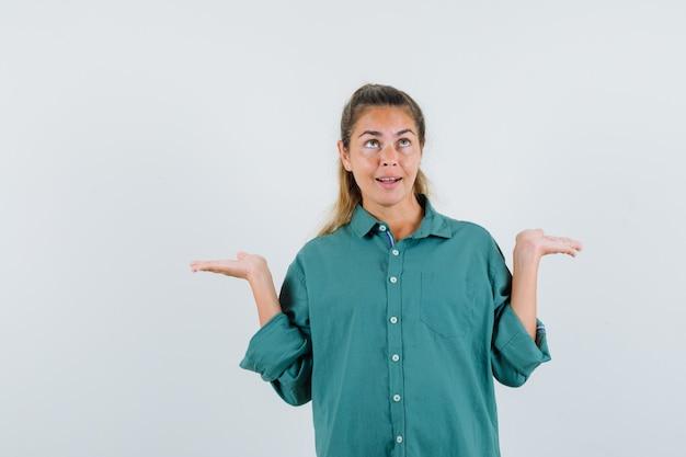 Mulher jovem mostrando um gesto desamparado com uma camisa azul e parecendo confusa