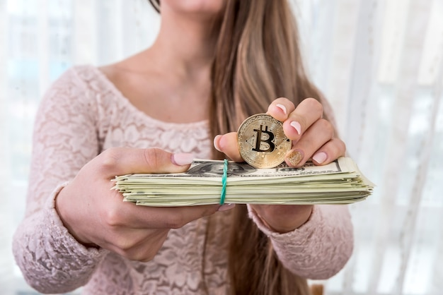 Mulher jovem mostrando um pacote de dólares e bitcoin dourado
