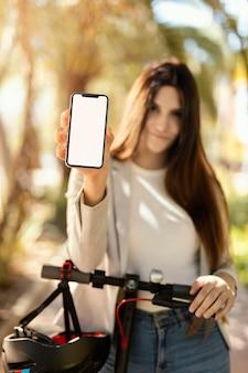 Mulher jovem mostrando um smarthphone em uma scooter elétrica na cidade