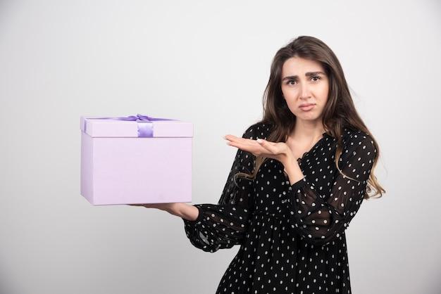 Mulher jovem mostrando uma caixa de presente roxa