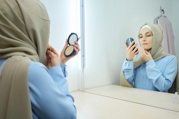 Mulher jovem muçulmana atraente em hijab bege e vestido azul tradicional, fazendo maquiagem e em frente ao espelho.