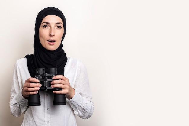 Mulher jovem muçulmana surpresa amigável em camisa branca e hijab segurando binóculo