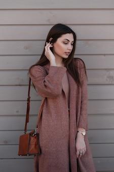 Mulher jovem muito bonita feminina alisa o cabelo e olha para baixo. linda garota com casaco longo elegante com bolsa de couro marrom elegante posa perto de prédio de madeira vintage na rua. roupa casual