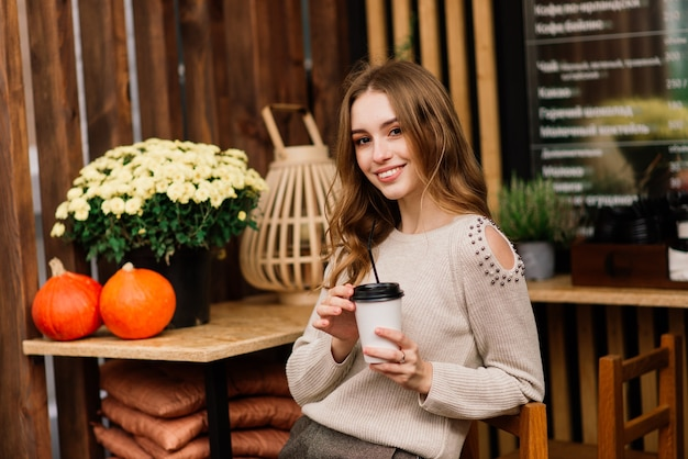Mulher jovem muito bonita, sente-se no café e beba café ou chá com croissant, vista frontal para a rua