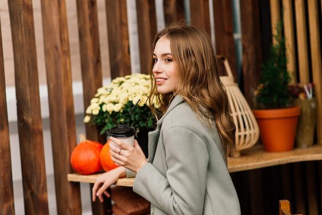 Mulher jovem muito bonita, sente-se no café e beba café ou chá com croissant