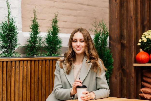 Mulher jovem muito bonita, sente-se no café e beba café ou chá, vista frontal da rua